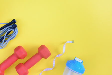 Photo pour A model with a place for text on a sports theme. Fitness background. Dumbbells, a water bottle, a skipping rope and a measuring tape are located on a bright yellow background. - image libre de droit