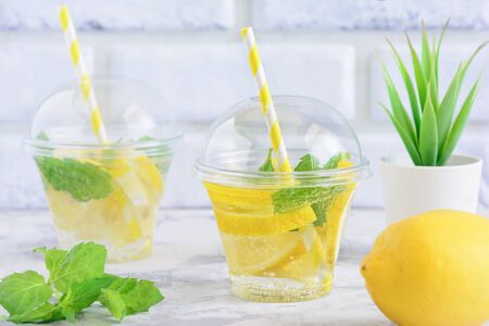 Foto de Refreshing Detox Citrus Mint Sassy Water Beverage. Organic Lemonade Served in Glass with Straw. Home plant on Table Background. Natural Belly Anti Bloating. Vegan Cleansing Drink Concept - Imagen libre de derechos