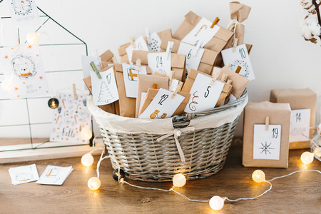 Foto de Advent calendar waiting for Christmas. Basket with envelopes with numbers and tasks for children standing on cabinet - Imagen libre de derechos