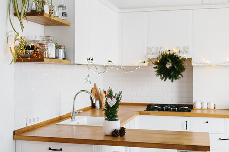 Photo pour Small Christmas tree in white flower pot white modern kitchen scandinavian style decorated for Christmas background. Cypress, Chamaecyparis lawsoniana Ellwoodii - image libre de droit