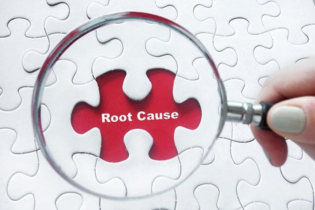Foto de Word Root Cause with hand holding magnifying glass over jigsaw puzzle - Imagen libre de derechos