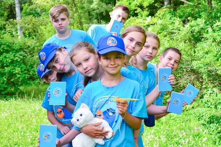 Photo pour Summer camp for gifted children - children's science city. In the photo, children in identical camp shirts are holding notebooks. - image libre de droit