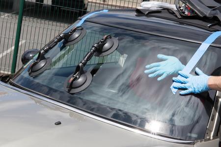 Foto de Glazier removing windshield or windscreen on a car - Imagen libre de derechos