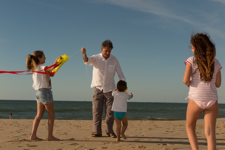 Two Generation Family Having Fun On Beach