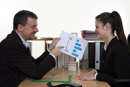 Two business people sitting in the office working in a team looking at balance sheet or assessment report.