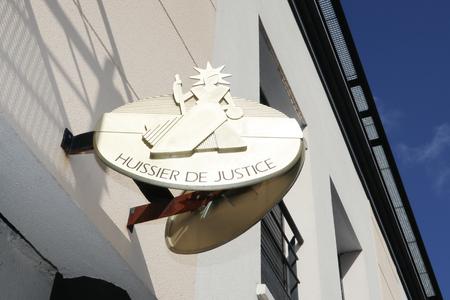 Foto de sign road bailiff plate on french building facade  huissier de justice means bailiff office - Imagen libre de derechos