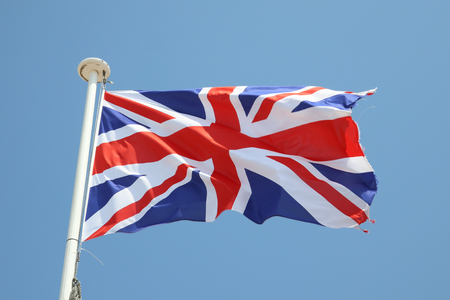 Foto de uk flag british on a mat in the wind and blue sky - Imagen libre de derechos
