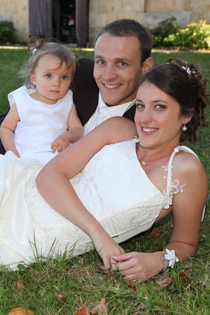 Photo pour wedding couple bride and groom sit on grass with girl child bridesmaid in white dress - image libre de droit
