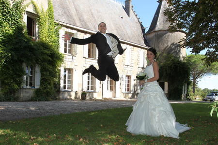 Photo pour front of ancient castle wedding couple play and groom jump which bride looking - image libre de droit
