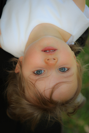 Photo pour young child girl play outdoor and puts her head upside down - image libre de droit