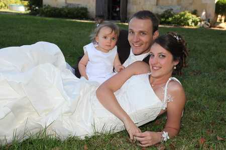 Photo pour happy bride and groom with their daughter girl lying on green grass garden park - image libre de droit
