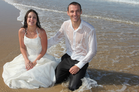 Photo pour Bride and Groom sitting in sand beach shore - image libre de droit