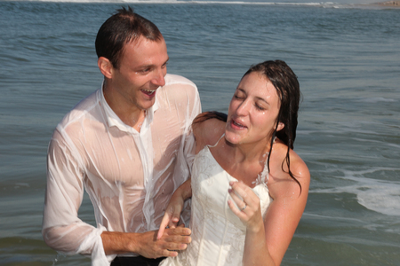 Photo pour youg married wedding couple swimming with marriage clothes and dress in sea beach - image libre de droit