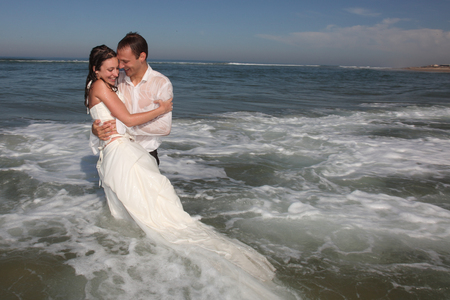 Photo pour Happy newlywed couple standing in water wedding groom and bride in love - image libre de droit