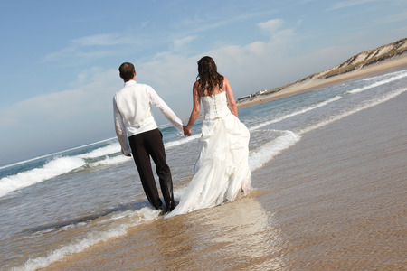 Photo pour Wedding couple walking on the beach in wedding dress - image libre de droit