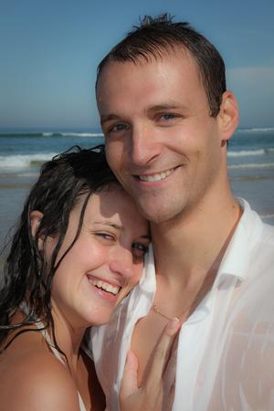 Photo pour Beautiful young wet couple on the sandy beach of the sea - image libre de droit