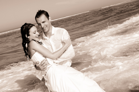 Photo pour Newlyweds sharing a romantic moment at the beach in black and white retro picture photo - image libre de droit