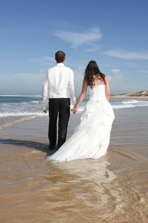 Photo pour Wedding couple on the sea beach back view - image libre de droit