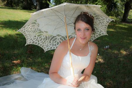 Photo pour cute bride with sun umbrella sit on grass on wedding day - image libre de droit