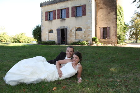 Photo pour beautiful couple in love in wedding day lying on green grass front of castle background - image libre de droit