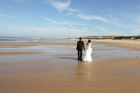 Photo pour back view Newlyweds sharing a romantic moment at the beach groom and bride walking on sand beach - image libre de droit