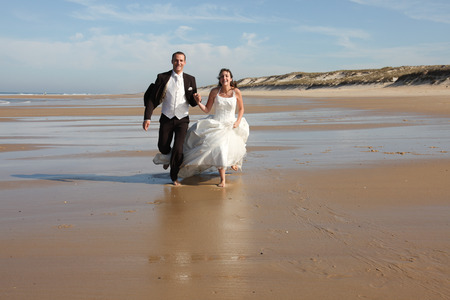 Photo pour bride and groom running on the sand at sea beach summer - image libre de droit