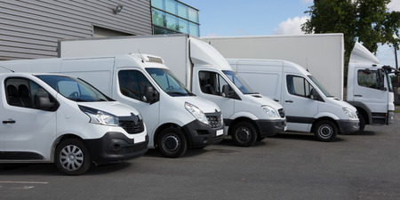 Photo pour White Delivery Trucks parked in Warehouse Building - image libre de droit