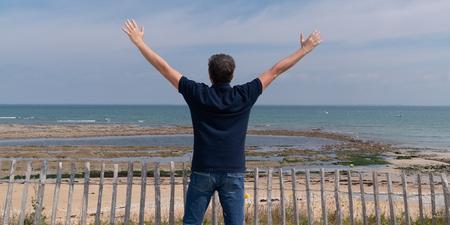Foto de happy man raise hands on beach background in feel good and freedom concept - Imagen libre de derechos