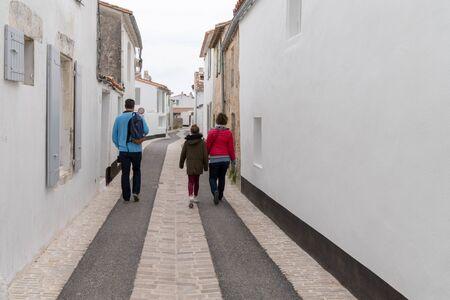 Photo pour back view tourist family walking on street at Saint Martin de Re village situated on Ile de Re in France - image libre de droit