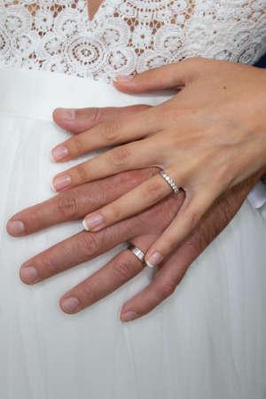 Photo pour wedding rings on bride groom hands on white dress background - image libre de droit