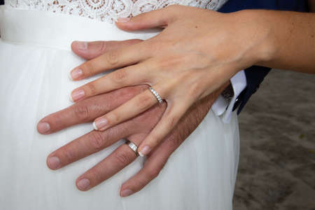 Photo pour wedding rings on bride and groom hands on marriage white dress background - image libre de droit