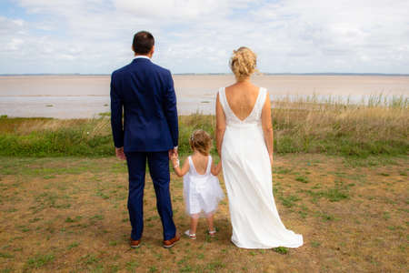Photo pour Happy wedding couple with child girl looking river coast in back view - image libre de droit