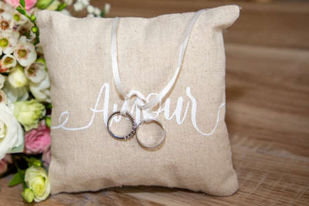 Photo pour wedding rings on brown natural pillow with ribbon on wooden table with amour text means love in french and flowers marriage bouquet - image libre de droit