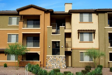 New 3-story condominium complex in gold and tan stucco with desert landscaping