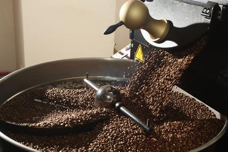 Foto de Freshly roasted coffee beans spilled out coffee roasting machines - Imagen libre de derechos