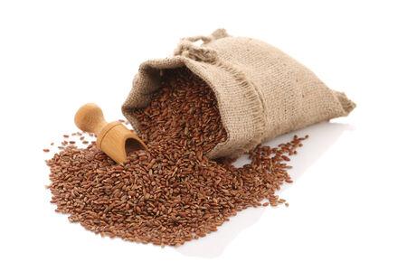 Foto de grade brown rice grain devzira scattered near the sack on a white background isolate - Imagen libre de derechos