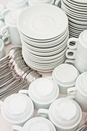 pile wihte tea tableware and spoons