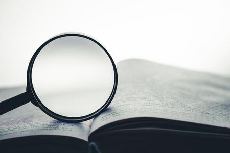 Foto de Magnifying glass on the open book background. Empty copy space inside. - Imagen libre de derechos
