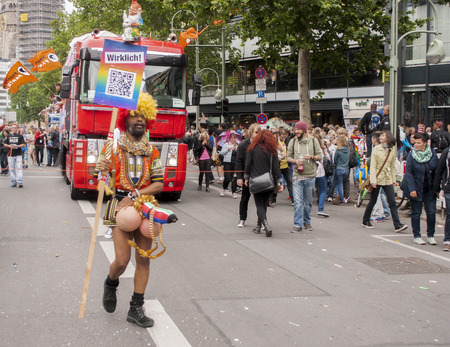 BERLIN, GERMANY - JUNE 21, 2014: Christopher Street Day. Crowd of people Participate in the parade celebrates gays, lesbians, bisexuals and transgenders. Prominent in the image, elaborately dressed participant.