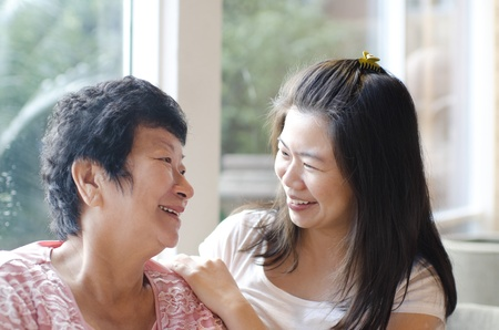 Photo for Asian family, adult daughter having conversation with senior mother indoor. - Royalty Free Image