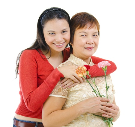 Asian mother holding carnation flower with her daughter isolated on white background