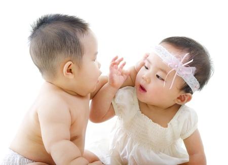 Photo pour Two Asian babies having baby talk - image libre de droit