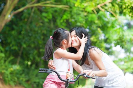 Photo pour Asian child kissing her mother. Asian family having fun outdoor, biking outdoor. - image libre de droit