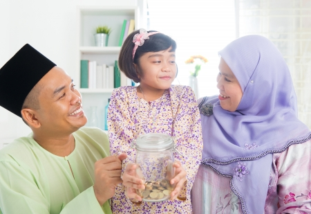 Islamic banking concept. Southeast Asian Malay family saving money at home. Muslim father, mother and daughter living lifestyle.