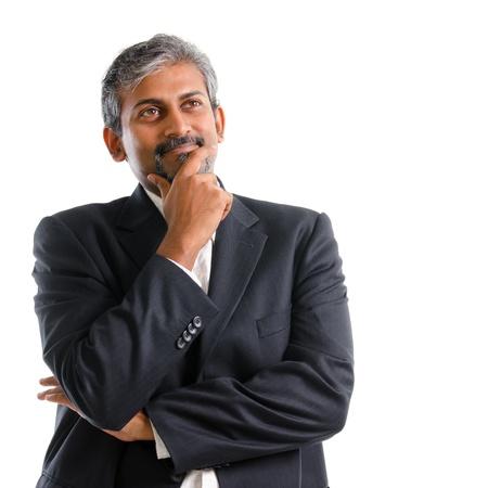 Foto de Attractive mature gray hair Indian business man thinking, isolated on white background - Imagen libre de derechos
