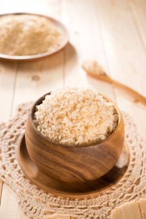 Foto de India organic basmati brown rice in wooden bowl on dining table. - Imagen libre de derechos