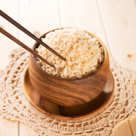 Foto de Close up cooked organic basmati brown rice in wooden bowl with chopsticks on dining table. - Imagen libre de derechos