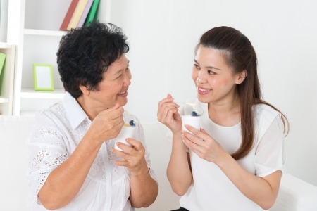 Photo for Eating yoghurt . Happy Asian family eating yogurt at home. Beautiful senior mother and adult daughter, healthcare concept. - Royalty Free Image