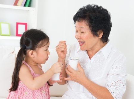 Photo for Eating yogurt. Happy Asian family eating yoghurt at home. Beautiful grandmother and grandchild, healthcare concept. - Royalty Free Image