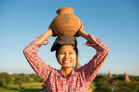 Photo for Portrait of Asian traditional female farmer carrying clay pot on head going back home, Bagan, Myanmar - Royalty Free Image